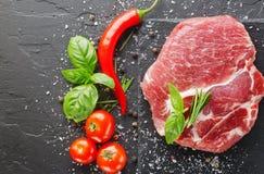 Schweinefleisch auf schwarzem Stein mit Pfeffer und Tomate Stockfoto