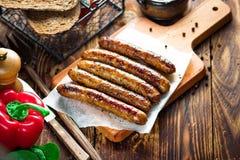 Schweinefleisch chipolata Großaufnahme von gebratenen Würsten Fleischteller Lizenzfreie Stockfotos