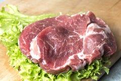 Schweinefleisch-Halsfleischsteaks auf Kopfsalat auf dem Hintergrund von Rettichen, Tomate, Pfeffer des roten Paprikas, gelbe Papr lizenzfreies stockbild