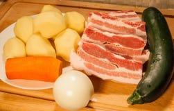 Schweinefleisch, Kartoffeln, Karottenzwiebeln und Zucchini Stockbilder