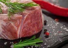 Schweinefleisch mit Rosmarin auf schwarzem Stein Lizenzfreies Stockfoto