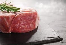 Schweinefleisch mit Rosmarin auf schwarzem Stein Stockfoto