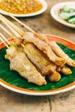 Schweinefleisch Satay auf hölzernem Hintergrund Stockfotos