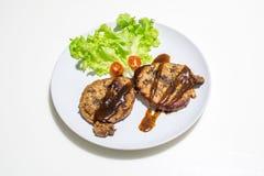 Schweinefleisch-Steak mit Salat Stockfotos