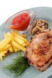 Schweinefleisch-Steak, Pommes-Frites und gegrillte Zwiebeln Stockfotos