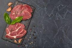 Schweinefleisch und Basilikum auf schwarzem Stein Stockfotos