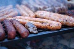 Schweinefleisch- und Rindfleischwürste, die über den heißen Kohlen auf einem Grill kochen Stockfotografie