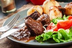 Schweinefleischeintopfgericht diente mit Kartoffeln und Gemüsesalat Stockfotografie
