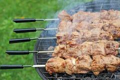 Schweinefleischgrill oder -Kebab auf dem Metall haftet Stockbilder