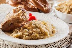 Schweinefleischknöchel mit gebratenem Sauerkraut und Tomaten stockbild