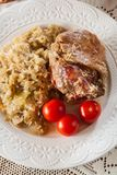 Schweinefleischknöchel mit gebratenem Sauerkraut und Tomaten lizenzfreies stockbild