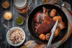 Schweinefleischknöchel mit Ofenkartoffeln und Zwiebeln in einer Wanne Auf dem Holztisch gibt es einen Becher Ale, Senf, Pesto, Kä stockfotos