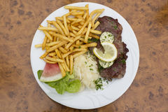 Schweinefleischkragensteak mit Kohlsalat, Kräuterbutter, Pommes-Frites Stockbild