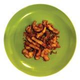 Schweinefleischstückchen im grünen Teller auf weißem Hintergrund Lizenzfreies Stockfoto