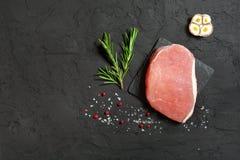 Schweinefleischsteak auf einem schwarzen Stein mit Pfeffer Stockfotos