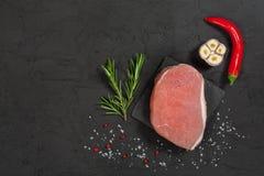Schweinefleischsteak auf einem schwarzen Stein mit Pfeffer Lizenzfreie Stockfotos