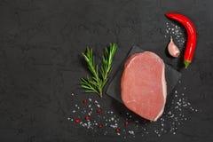 Schweinefleischsteak auf einem schwarzen Stein mit Pfeffer Lizenzfreies Stockbild