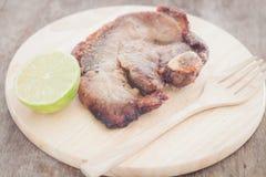 Schweinefleischsteak auf hölzerner Platte Stockfoto