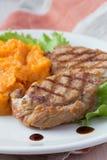 Schweinefleischsteak briet auf Grill mit den gestampften Süßkartoffeln, geschmackvoll stockbild