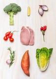 Schweinefleischsteak des rohen Fleisches und Frischgemüsebestandteile auf weißem hölzernem Hintergrund Lizenzfreie Stockbilder