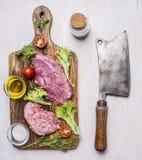 Schweinefleischsteak mit Gemüse und Kräuter, Fleischmesser und Gabel, auf einem Schneidebrett mit Ölgewürzen und Fleischbeil auf  Lizenzfreie Stockfotos