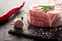 Schweinefleischsteak mit Knoblauch auf einem schwarzen Stein Stockfotografie