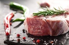 Schweinefleischsteak mit Rosmarin auf einem schwarzen Stein Stockbild