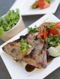 Schweinekotelett, Petersilienschüssel und Gemüse Stockbilder