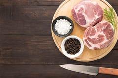 Schweinekotelettsteak der Draufsicht rohes auf Schneidebrett und Messer auf woode Stockbilder