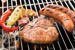 Schweinekotelettsteak und -gemüse mit Wurst auf einem lodernden BBQ-gril Stockfotografie