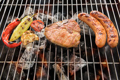 Schweinekotelettsteak und -gemüse mit Wurst auf einem lodernden BBQ-gril Stockfotos