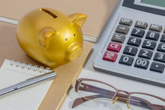 Schweinsparschwein, Taschenrechner, Telefon, Notizbuch, Stift, Gläser, Konzept des Einsparungsgeldes Lizenzfreies Stockbild