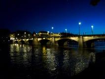 Schweiz Basel, UPPLYST mellersta BRO ÖVER Rhine River A Royaltyfria Foton
