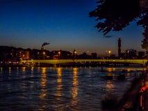 Schweiz Basel, UPPLYSTA BYGGNADER VID Rhine River MOT Fotografering för Bildbyråer