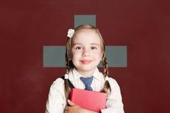 Schweiz begrepp med liten flickastudenten med boken mot den schweiziska flaggabakgrunden royaltyfria bilder