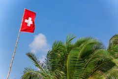 Schweiz flagga som blåser i vinden på en bakgrund för blå himmel Arkivbilder
