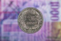 2 schweizare Franc Coin med 1000 schweizare Franc Bill som bakgrund Royaltyfri Bild