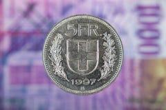 5 schweizare Franc Coin med 1000 schweizare Franc Bill som bakgrund Arkivfoto