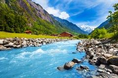 Schweizare landskap med flodströmmen och hus royaltyfri foto