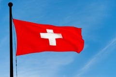 Schweizareflagga som vinkar över blå himmel Royaltyfria Bilder