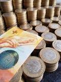 Schweizer Banknote von zehn Franken und Staplungsmünzen von zehn mexikanischen Pesos stockbilder