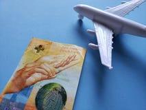 Schweizer Banknote, weißes Plastikflugzeug und blauer Hintergrund lizenzfreie stockfotografie