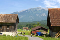 Schweizer Bauernhof und Pilger in der Alpen-Berglandschaft Stockfotografie
