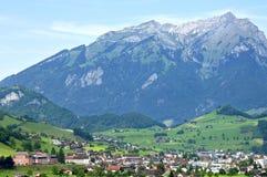 Schweizer Dorf-Ansicht von Stans mit Berg Stanserhorn stockbild