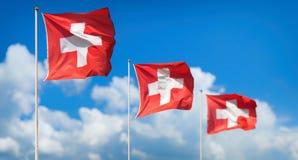 Schweizer Flaggen - Flaggen von der Schweiz wellenartig bewegend in Wind stockbilder