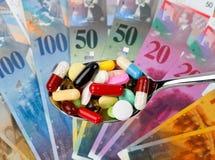 Schweizer Franc und Tabletten Stockfotos