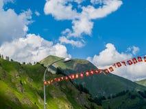 Schweizerbürgerflaggengirlande gegen die Schweizer Alpen bei Samnaun, die Schweiz Lizenzfreies Stockbild