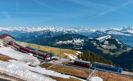 Schweizisk bergjärnväg- och vårpanoramautsikt av snö-korkade berg i fjällängarna royaltyfri foto