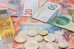 Schweizisk franc anmärkningar och mynt med nya tjugo och femtio schweizisk francräkningar Arkivbilder