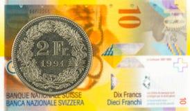 2 schweizisk franc mynt mot 10 schweizisk franc sedel arkivbilder